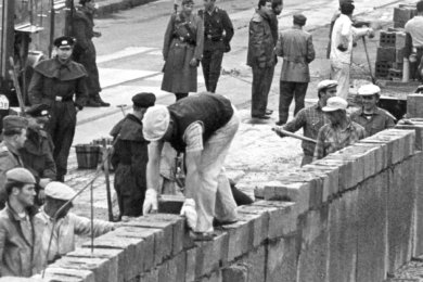 Eine Ostberliner Maurerkolonne arbeitet an der sowjetisch-amerikanischen Sektorengrenze am Potsdamer Platz.