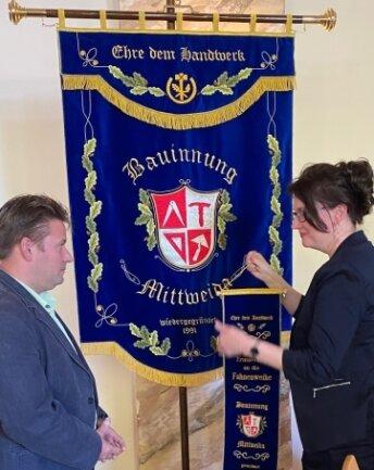 Sylvia Friedrich und Jörg Eulitz mit der neuen Fahne der Bauinnung Mittweida.