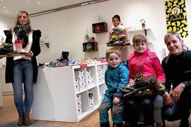Im Schuhladen für Kinder von Stephan Bräutigam (l.) sind seit Wochen keine Kunden mehr ein- und ausgegangen. Freude schenkte der Zwönitzerin ein Blumengruß der Diakonie, den Pflegedienstleiterin Doreen Haufe (hinten) mit Aline Roth und ihren Kindern Hannah sowie Henri überbrachte.