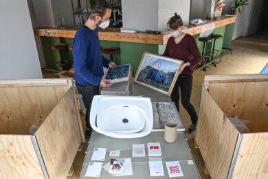 Robert Verch und Ulrike Brantl vom Klub Solitär sichten die Kunstwerke in den Holzboxen. In den kommenden Tagen soll daraus eine Ausstellung in den Schaufenstern des Lokomov entstehen.
