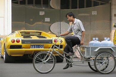 Kontraste in Peking: Ein Dreirad-Auslieferungsfahrer strampelt an einem Lamborghini vorüber, dessen Kaufpreis von über 200.000 Euro wohl seinem 200-fachen Jahreseinkommen entspricht. In Chinas Volkskongress sitzen viele Milliardäre und Multimillionäre, die jedes Jahr reicher werden.