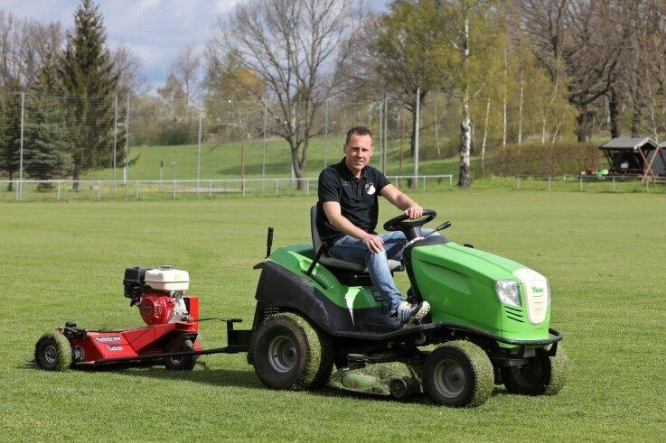 Ein typisches Bild auf Dorf-Sportplätzen: Vereinschef Eric Hofmann kümmert sich persönlich um die Rasenpflege in Niederlungwitz.