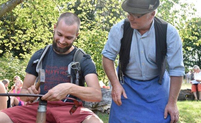 Michael Beyer (rechts) vom Sensendengelverein Schwarzbach/Erzgebirge erklärt Florian Kaiser aus Markneukirchen das fachgerechte Dengeln einer Sense.