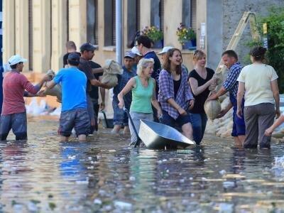 Helfer schichten Sandsäcke in einer überfluteten Straße in Magdeburg gegen das steigende Hochwasser auf.