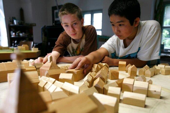 Peter Zimmermann (l.) und Anh Lam Nguyen von der Oederaner Gemeinschaftsschule bei letzten Arbeiten am Stadtmodell, das aus insgesamt 400 hölzernen Häuschen besteht.