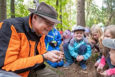 Tim Buchau und die Klasse 3 beim Riechen des Waldbodens.