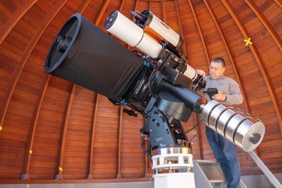 Olaf Graf am Herzstück der neuen Beobachtungstechnik unter der Kuppel der Sternwarte Rodewisch: ein 500-mm-Spiegelteleskop, das zusammen mit Refraktor, Astrograph und Kameratechnik auf einer Montierung steht, die per Computer gesteuert wird.