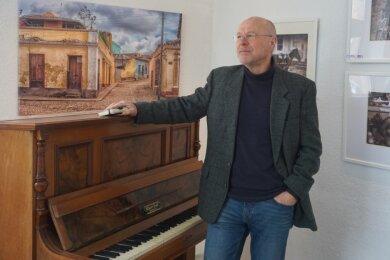 Hinter Arno Bast, Chef des Deckerberg-Vereins in Mittweida, hängen die Werke des Gersdorfer Fotografen Franko Finster. Das Klavier neben ihm hat der Verein erst kürzlich erworben. Es kann von jedem, der möchte, genutzt werden.