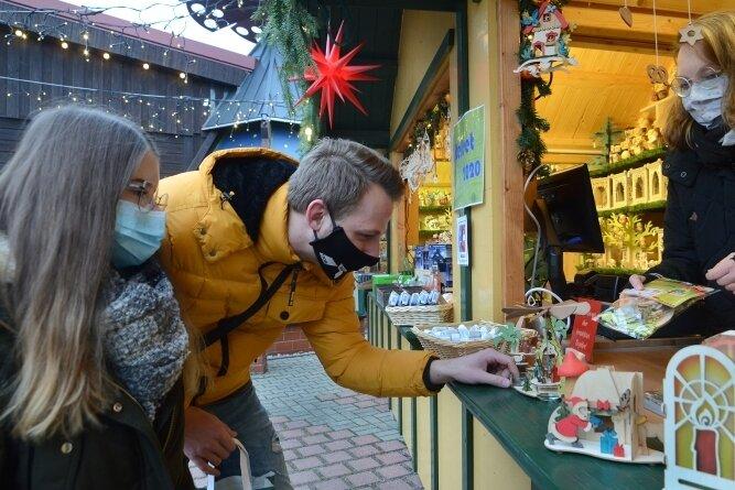 Melissa Poser und Lucas Nürnberger lassen sich von Denise Croy an einem der Verkaufsstände vor der Drechslerei beraten. Normalerweise finden in der kleinen Budenstadt an den Adventswochenenden die Wichteltage statt.