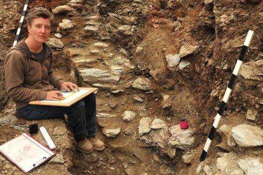 """Sonja Matson, Archäologin vom Landesamt für Archäologie Dresden, hat nahe der Burg Hoheneck eine Mauer mit Ecke (auf dem Foto rechts unten) freigelegt. """"Das ist eine echte Überraschung"""", so die Expertin."""