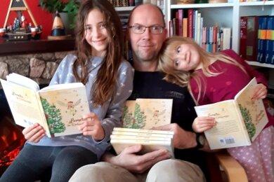 """Helene (l.) und Hermine können es kaum erwarten, dass ihr Vater das Buch Geschichte vorliest. Ralph Bennewitz hat das Weihnachtsmärchen """"Lametta, die Weihnachtsfee"""" selbst geschrieben."""
