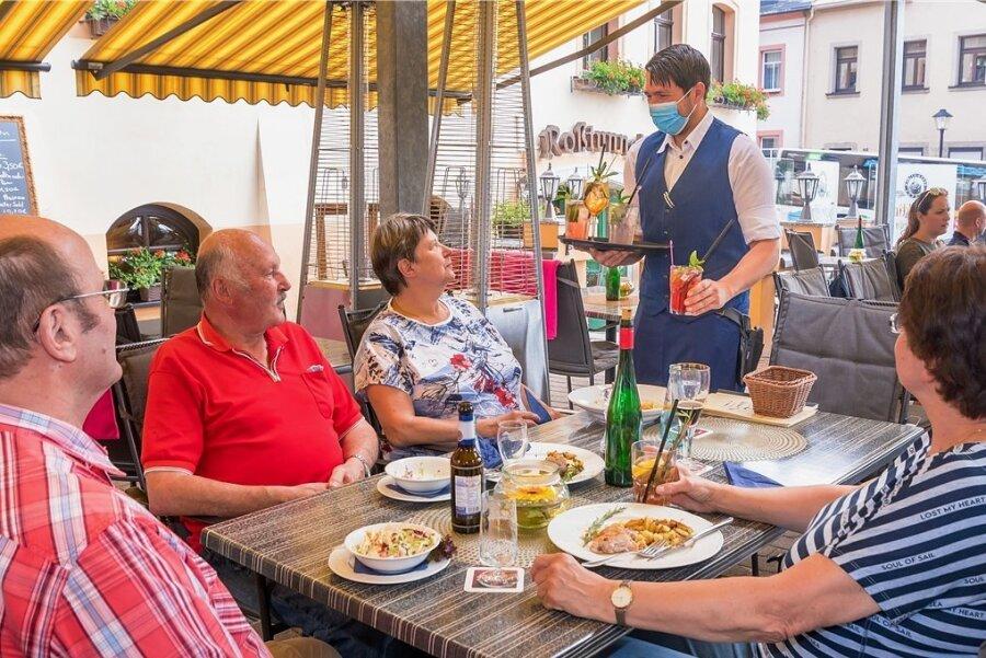 """Endlich wieder Gäste: Restaurantleiter Marcel Petke serviert auf der Terrasse vom """"Weißen Roß"""" in Marienberg den Scharfensteiner Familien Urban (vorn) und Albrecht zum Essen hausgemachte Limonaden."""