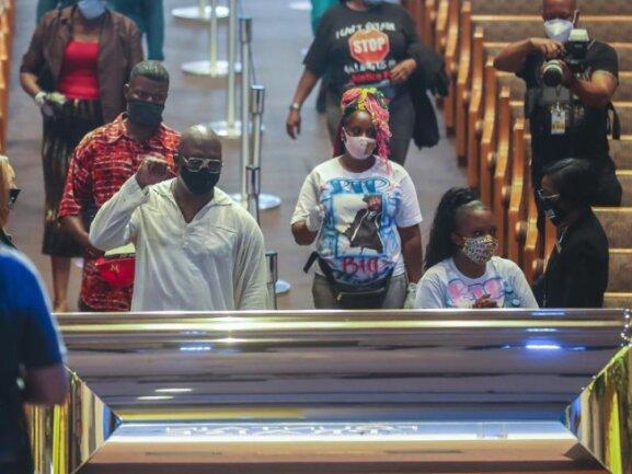 Trauergäste stehen vor dem goldfarbenen Sarg in der «The Fountain of Praise» Kirche.