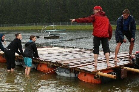 Im Naturbad in Johanngeorgenstadt ließ sich das Team beim Umbau des Floßes auch vom widrigen Wetter nicht aufhalten.