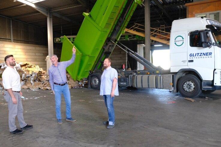 """Anlieferung von Pappe und Papier in einer Glitzner-Halle am vogtländischen Müllstandort in Schneidenbach. Immer wieder ist brandgefährlicher, oft noch mit Akkus ausgestatteter Elektronikschrott als Beifang dabei. """"Das gehört nicht in die blaue Tonne"""", sagt KEV-Geschäftsführer Jens Gerisch (Mitte)."""
