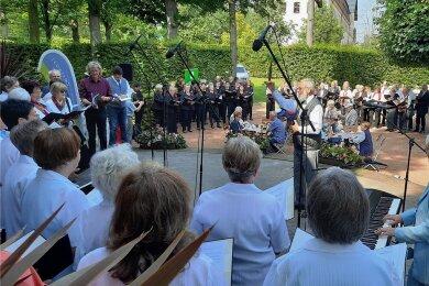 Unter Leitung von Michael Albrecht (Mitte) sangen zu Beginn des diesjährigen Sängertreffens im Schlosspark Lichtenwalde alle teilnehmenden neun Chöre gemeinsam mit dem Publikum. Begleitet wurden sie von der Rochlitzerin Ursula Barz am Klavier (r.), die mit ihren 81 Jahren zu den Urgesteinen dieser Veranstaltungsreihe gehört.