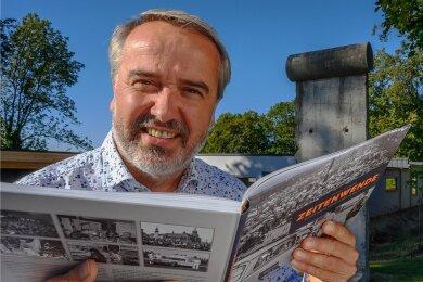 """Andreas Kretschel mit dem Buch """"Zeitenwende"""", im Hintergrund erinnert ein Stück Berliner Mauer auf seinem Grundstück an die Geschichte."""