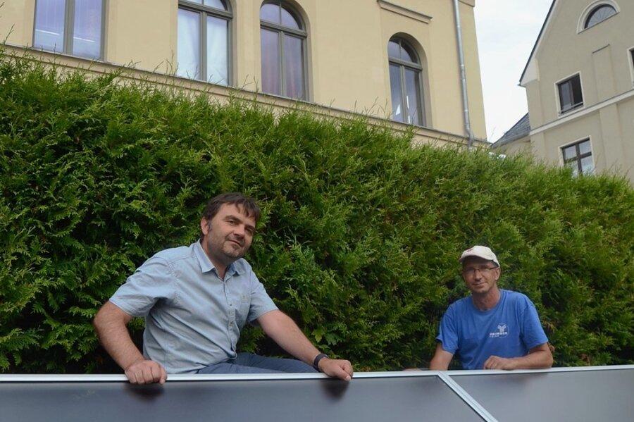 Alexander Spitzner von der TWV (links) mit Monteur Steffen Fröhlich an den Solarmodulen, die an der Böschung hinter der Stadtbibliothek Treuen angebracht sind. In den Modulen wird die Luft der Solarlüftung erwärmt, mit deren Hilfe der Keller des Bücher trockengelegt werden soll.