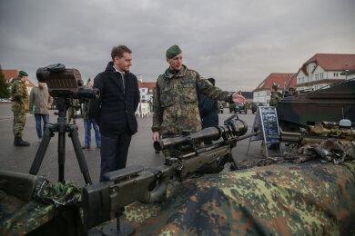 Michael Kretschmer lässt sich von Oberstabsgefreiter Frank Alperstedt die Ausrüstung eines Scharfschützen erklären.