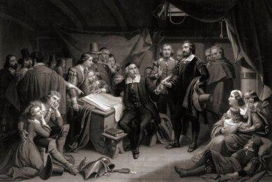 """Die Pilgerväter unterschreiben 1620 an Bord der """"Mayflower"""" eine Übereinkunft für ihr künftiges Gemeinwesen."""