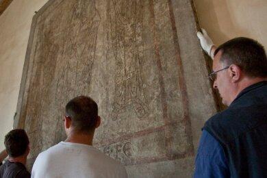 """<p class=""""artikelinhalt"""">Restaurator Wilfried Sitte (rechts) und sein Team haben in der vergangenen Woche das wertvolle Putzritzbild im Kloster Altzella mit größter Sorgfalt von der Wand abgenommen, um es nach Naumburg zu transportieren.</p>"""