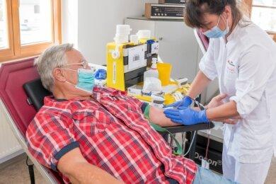 Schwester Katy zapfte Jürgen Meißner bei seiner 100. Spende einen halben Liter Blut ab.