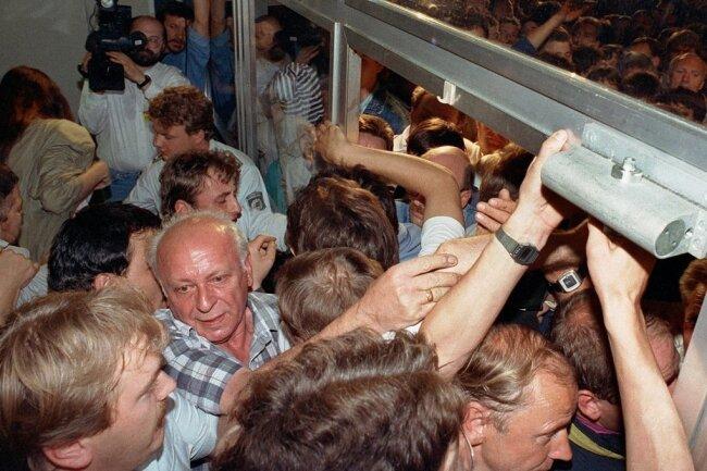 Riesenandrang auf die Ost-Berliner Filiale der Deutschen Bank: Es gab Verletzte, Scheiben barsten. Mit der am 1. Juli 1990 vollzogenen Währungsunion war die Wiedervereinigung der beiden deutschen Staaten einen entscheidenden Schritt nähergerückt. Der Tag begann überall in Ostdeutschland mit einem regelrechten Ansturm auf das begehrte neue Geld.