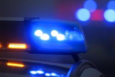 Ein Polizeiauto mit eingeschaltetem Blaulicht steht an einer Unfallstelle.