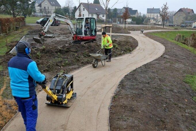 Jens Scheeler (vorn) und Frank Lay legen die sandgeschlämmten Wege im parkähnlichen Gelände des neuen Festplatzes an.