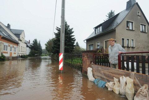 Hochwasser in der Straße des Friedens in Niederlungwitz: Anwohner Werner Finzel blickte besorgt auf die Flut.