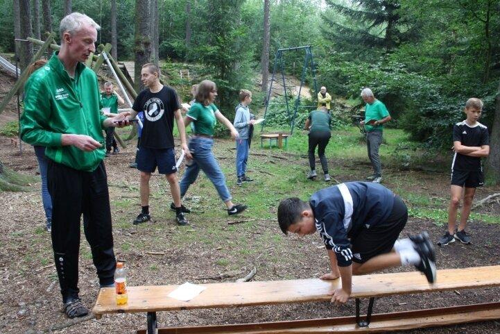 Vereinschef Tino Winkler (links) zählt, wie oft Tyler Plönzke aus Wilkau-Haßlau über die Bank springt.