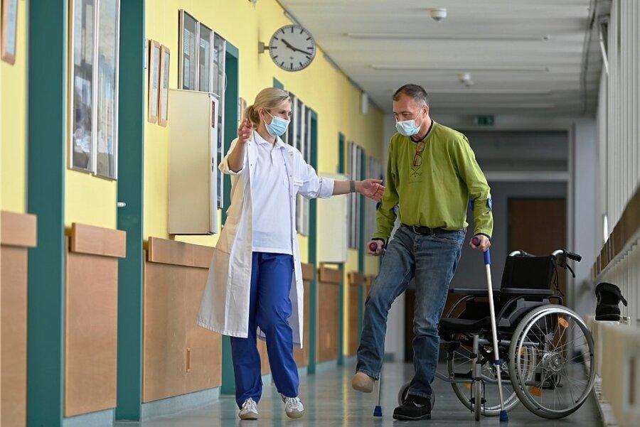 Dr. Elisabeth Wendt vom Diabetischen Fußzentrum der Helios Weißeritztal-Klinik Freital unterstützt den Dresdner Patienten bei seinen ersten Gehversuchen ohne Rollstuhl.