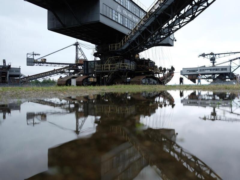 Ein ausgestelltes Bergbaugerät spiegelt sich in Ferropolis in einer Pfütze.