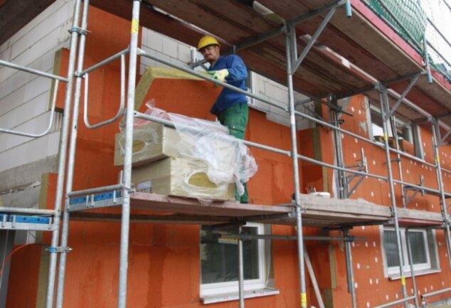 """<p class=""""artikelinhalt"""">Es geht voran: Sören Päßler von der Firma Fritzsche aus Hohndorf bringt Mineralwolle-Dämmplatten an die Fassade der Turnhalle an. </p>"""