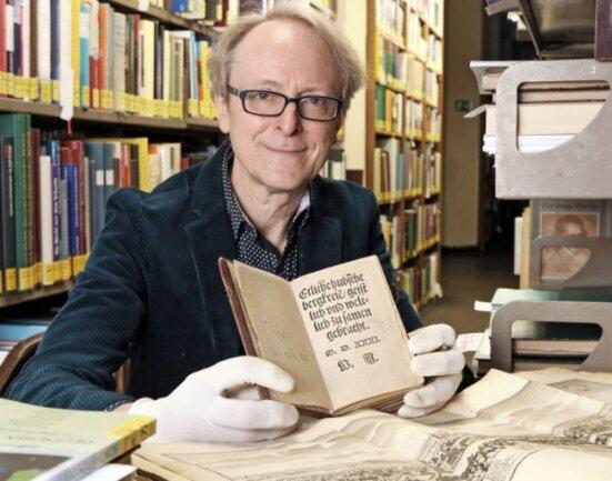 Bibliotheksleiter Lutz Mahnke hält jenes Büchlein aus dem Jahr 1531 in Händen, in dem das Steigerlied seine Weltpremiere fand.