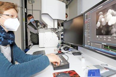 Nora Brachhold, wissenschaftliche Mitarbeiterin im Freiberger Neubau, und Ralf Haak von der Firma Tescan probieren die Funktionen eines Hochleistungs-mikroskopes aus.