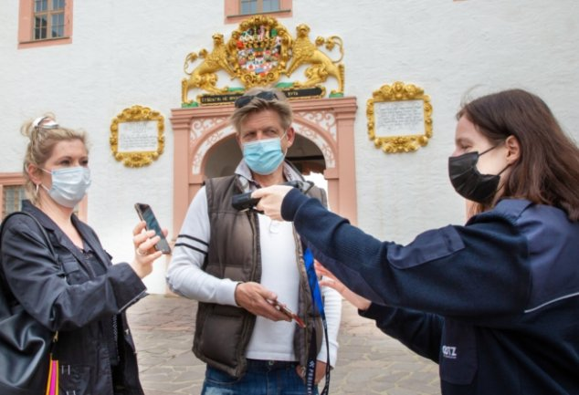 Claudia Zakowsky (l.) und Marius Marx aus Chemnitz ließen sich in Augustusburg testen und genossen nach dem negativen Ergebnis die wiedergewonnenen Freiheiten im Schloss. Sandra Eschrich scannt den QR-Code.