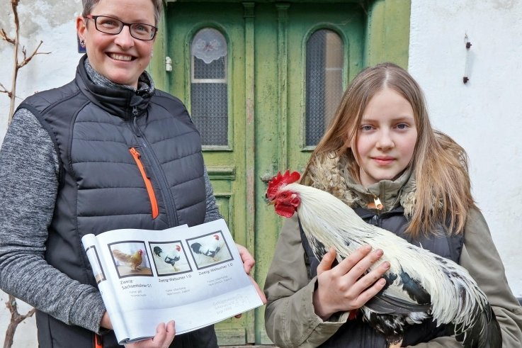 Stolz präsentiert Nele ihren Hahn der Rasse silberfarbige Zwerg Welsumer, der im Ausstellungsbuch des Vereins, das Mutter Diana Irmisch in den Händen hält, mit vertreten ist.