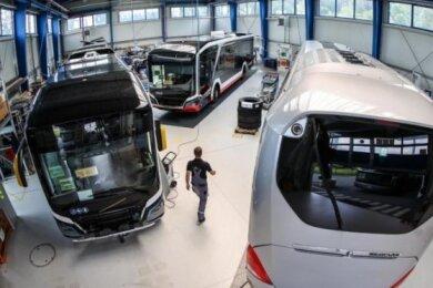 Ein Mitarbeiter geht durch eine Halle mit Elektrobussen von MAN.