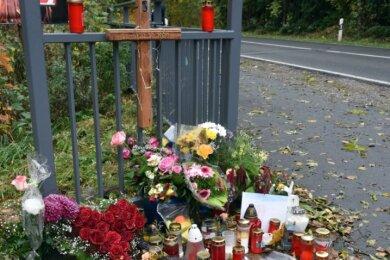 Am Eingang zum Grundstück, auf dem ein Haus brannte, sind Blumen und Kerzen für das 14-jährige Mädchen abgelegt worden, das beim Feuer am 21. Oktober gestorben ist. Ein Holzkreuz erinnert an die Tragödie.