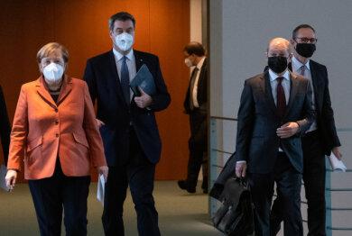 Auf dem Weg zur Pressekonferenz nach der Schaltkonferenz von Bundeskanzlerin und Bundesregierung mit den Ministerpräsidenten der Länder (von links): Bundeskanzlerin Angela Merkel (CDU), Markus Söder (CSU), Ministerpräsident von Bayern, Olaf Scholz (SPD), Bundesfinanzminister, und Michael Müller (SPD), Regierender Bürgermeister von Berlin.