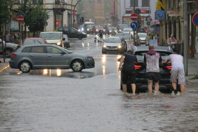 Nach dem Unwetter steckte ein Fahrzeug in den Fluten auf der Auer Bahnhofstraße fest. Fußgänger schoben das Auto aus dem Wasser.