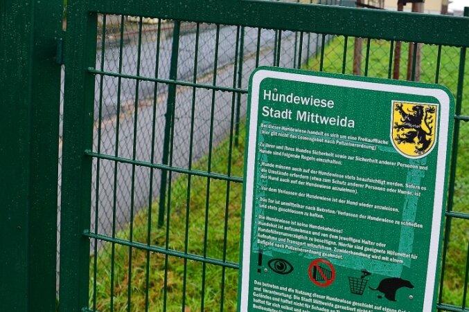 Im Zaun um die Hundewiese gibt es mehrere Schlupflöcher. Ein Schild am Eingang weist Halter auf ihre Aufsichtspflicht hin.