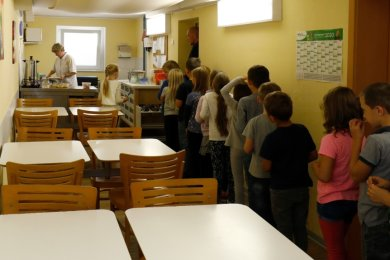 Bräunsdorfer Grundschüler warten in der benachbarten Kita darauf, dass sie sich ihr Mittagessen nehmen können. In dem schlauchförmigen Raum finden nur etwa 20 Kinder Platz, sodass die vier Klassen nacheinander essen müssen.