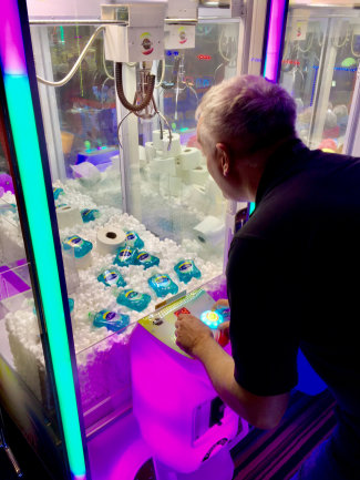 Ein Mann spielt an einem Spielautomaten, in dem mehrere Flaschen Desinfektionsmittel liegen. Der Betreiber eines britischen Ferienparks hat als Reaktion auf Hamsterkäufe wegen der Covid-19-Epidemie seine Spielautomaten mit Toilettenpapier und Desinfektionsmittel befüllt. Wo es sonst gilt, mit einem Greifarm Teddybären und andere Stofftiere aus dem Automaten zu angeln, sind jetzt die weißen Rollen und Flaschen mit Desinfektionsgel zu gewinnen.