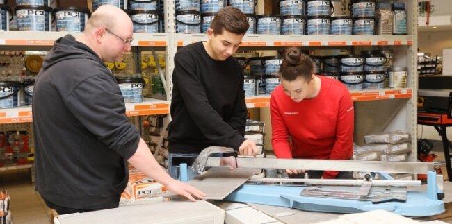 Mitarbeiter André Völkel (l.), der selbst einst bei dem Zwickauer Baustoffhändler ausgebildet wurde, kann sich gut in die beiden Azubis Pierre Eisert und Alina Giese hineinversetzen.