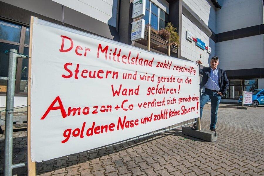 """Rings um das Möbelhaus Illing in Aue stehen Bannern, die auf die angespannte Lage vieler Händler aufmerksam machen sollen. """"Spontan ausgedacht"""" hat sich die Sprüche auf den Plakaten der Mitinhaber Michael Peter (Bild)."""