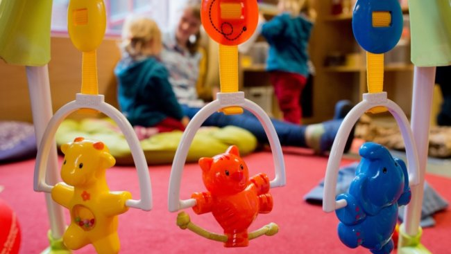 Kinderspielzeug hängt im Gruppenraum einer Kita - ein Symbolbild für Kinderbetreuung.
