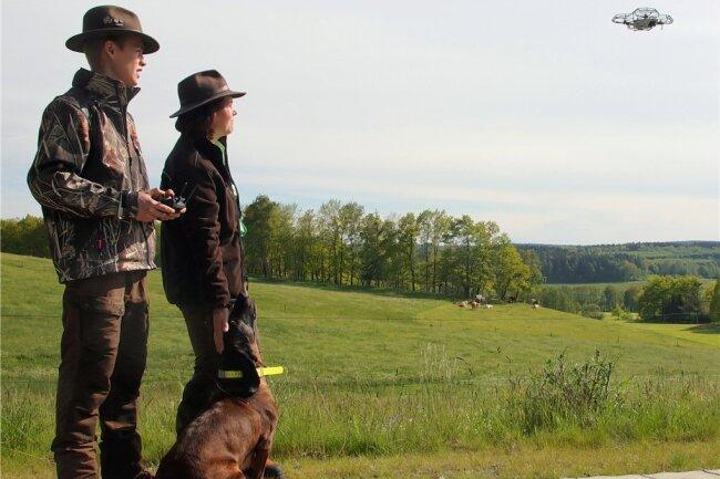 Vom Rand der Grünfläche aus beobachten Carljohannes und Kathleen Rotter, wie ihre Drohne die Wiese überfliegt, um versteckte Rehkitze ausfindig zu machen.