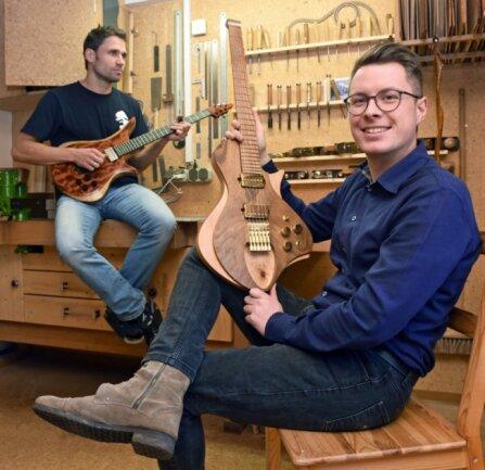 Roy Fankhänel aus Oelsnitz (links) und Tim Walter aus Burgstädt entwerfen und bauen E-Gitarren. Sie setzen dabei auch auf besonderes Design. In der Werkstatt von Fankhänel entstehen die Instrumente, die Walter in Burgstädt entwirft. Walter präsentiert ein Modell, in dessen Korpus ein Astloch zu sehen ist.